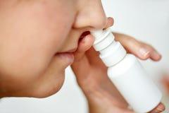 Stäng sig upp av den sjuka kvinnan som använder nasal sprej fotografering för bildbyråer