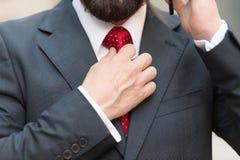 Stäng sig upp av den skäggiga mannen som trycker på det röda bandet, medan tala på telefonen royaltyfri fotografi