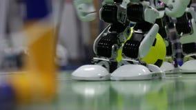 Stäng sig upp av den smarta humanoid robotfoten som spelar fotboll stock video