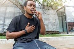 Stäng sig upp av den stressade mörkhyade mannen i svart T-tröja som talar vid mobiltelefonen arkivfoto