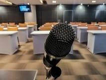 Stäng sig upp av den svarta mikrofonen lokaliseras framme av mötesrummet fotografering för bildbyråer