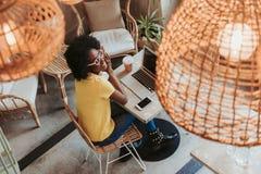 Stäng sig upp av den unga afrikanska kvinnan som arbetar med digitala grejer i kafeteria royaltyfri foto