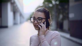 Stäng sig upp av den unga attraktiva kvinnan som talar, genom mobiltelefonen och att le lager videofilmer