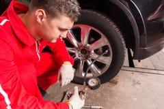 Stäng sig upp av den unga auto mekanikern som kontrollerar lufttrycket av en t Royaltyfria Bilder