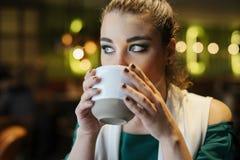 Stäng sig upp av den unga brunettkvinnan som dricker kaffe royaltyfria foton