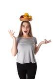 Stäng sig upp av den unga förvånade kvinnan som rymmer en träbunke med frukter: äpplen apelsiner, citron Vitaminer och sunt äta Arkivfoton