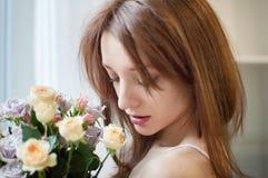 Stäng sig upp av den unga kvinnlign som är tonårig med blommor nära fönstret hemma royaltyfria foton
