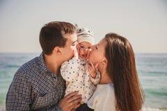 Stäng sig upp av den unga lyckliga älska familjen med den lilla ungen i mitt och att kyssa sig nära havet, lyckliga den conc livs Royaltyfri Bild