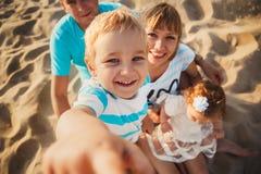 Stäng sig upp av den unga lyckliga älska familjen med små ungar i mitt och att ha gyckel på stranden tillsammans nära havet, lyck arkivfoto