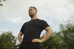 Stäng sig upp av den unga mannen i svart sportswear som kopplar av på parkera, når du har övat fotografering för bildbyråer