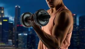 Stäng sig upp av den unga mannen med hanteln som böjer biceps Fotografering för Bildbyråer