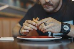 Stäng sig upp av den unga mannen som äter hamburgare- och fransmansmåfiskar på kafét Bekläda beskådar royaltyfria bilder