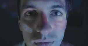 Stäng sig upp av den unga mannen som hemma håller ögonen på en video eller en film på TV eller en datorbildskärm Reflexion på han stock video