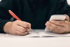 Stäng sig upp av den unga studenten med smartphonen som skriver till anteckningsboken Royaltyfria Bilder