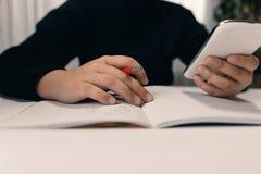 Stäng sig upp av den unga studenten med smartphonen som skriver till anteckningsboken Arkivfoton