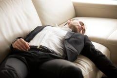 Stäng sig upp av den utmattade affärsmannen som lägger på soffan Fotografering för Bildbyråer