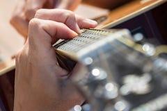 Stäng sig upp av den vänstra handen av en gitarrist som spelar ackord royaltyfri foto