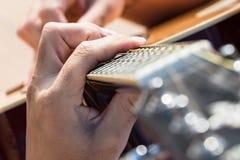 Stäng sig upp av den vänstra handen av en gitarrist som spelar ackord royaltyfri fotografi