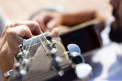 Stäng sig upp av den vänstra handen av en gitarrist som spelar ackord arkivfoton