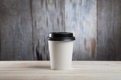 Stäng sig upp av den varma pappers- koppen för svart kaffe på på trätabellen Arkivbild
