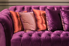 Stäng sig upp av den violetta sammetsoffan och kuddar Royaltyfri Fotografi