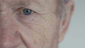 Stäng sig upp av det öppna blåa ögat av gamala mannen som ser kameran på bakgrund stock video
