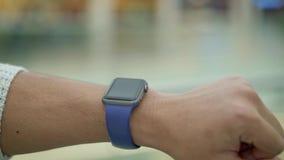Stäng sig upp av det manliga fingret som nallar till vänstersidan på smartwatch lager videofilmer