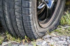 Stäng sig upp av det plana gummihjulet på en bil på grusvägen Fotografering för Bildbyråer