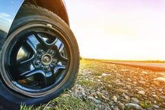Stäng sig upp av det plana gummihjulet på en bil på grusvägen Arkivfoton