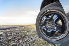 Stäng sig upp av det plana gummihjulet på en bil på grusvägen Arkivbild