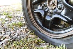 Stäng sig upp av det plana gummihjulet på en bil på grusvägen Royaltyfri Fotografi