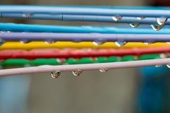 Stäng sig upp av droppar på färgrik torkdukehängare i regnig dag Royaltyfri Foto