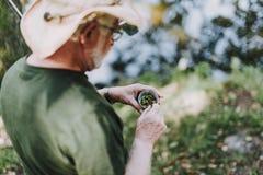 Stäng sig upp av en åldrig sportfiskare som rymmer en ask med beten royaltyfria foton