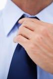 Stäng sig upp av en affärsman som reparationr hans tie Arkivfoto