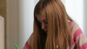 Stäng sig upp av en allvarlig ung flicka, medan dra på papper arkivfilmer