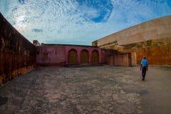 Stäng sig upp av en asfull rosa vägg på det fria, med en man som går på det fria i den Amber Fort slotten som lokaliseras i Amer Arkivfoton