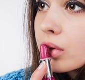 Stäng sig upp av en attraktiv flicka som hon öppnade hennes mun och satte dem röd läppstift leenden Bruntögon Fotografering för Bildbyråer