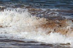 Stäng sig upp av en avbrottsvåg på kusten Arkivbild