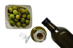 Stäng sig upp av en bunke av olivgrön och extra jungfrulig olivolja i flaska royaltyfri bild