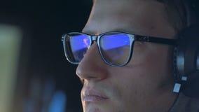 Stäng sig upp av en dataspel som reflekterar i gamer'sens exponeringsglas arkivfilmer