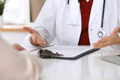 Stäng sig upp av en doktor och patienthänder, medan diskutera sjukdomshistorier efter vård- undersökning Royaltyfri Fotografi