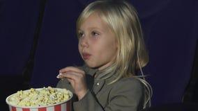 Stäng sig upp av en förtjusande liten flicka som äter popcorn medan på filmteatern royaltyfri foto