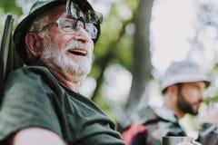 Stäng sig upp av en glad gamal man som utomhus vilar arkivfoto