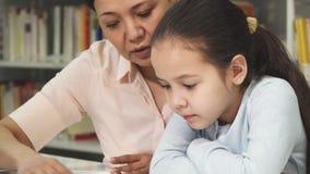 Stäng sig upp av en gullig liten flicka som läser en bok med hennes moder royaltyfri foto