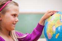 Stäng sig upp av en gullig schoolgirl som ser ett jordklot Arkivbild