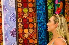 Stäng sig upp av en härlig blond ung kvinna som ser andean traditionella kläder, färgrik tygbakgrund royaltyfria bilder