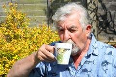Stäng sig upp av en hög man som dricker kaffe Royaltyfri Foto