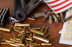 Stäng sig upp av en hagelgevär, och en revolver, kassettbälte med kulor med delen av suddig Förenta staterna sjunker på en översi Royaltyfri Bild
