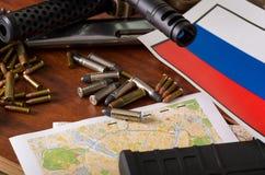 Stäng sig upp av en hagelgevär och en revolver, kassettbälte med kulor med en ryssflagga på en översikt, på trätabellen Arkivbilder