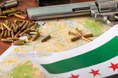 Stäng sig upp av en hagelgevär och en revolver, kassettbälte med kulor med en suddig Irak flagga på en översikt, på trätabellen Royaltyfria Foton